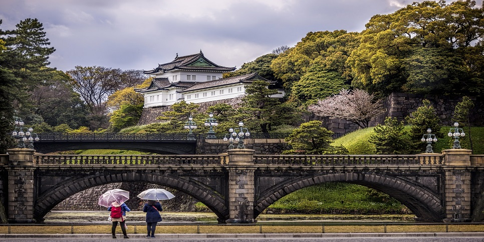 Tokyo, Japan - April 11, 2015: Two unidentified young ladies with their eye catching umbrellas contemplate the imposing Imperial Palace in Tokyo, Japan